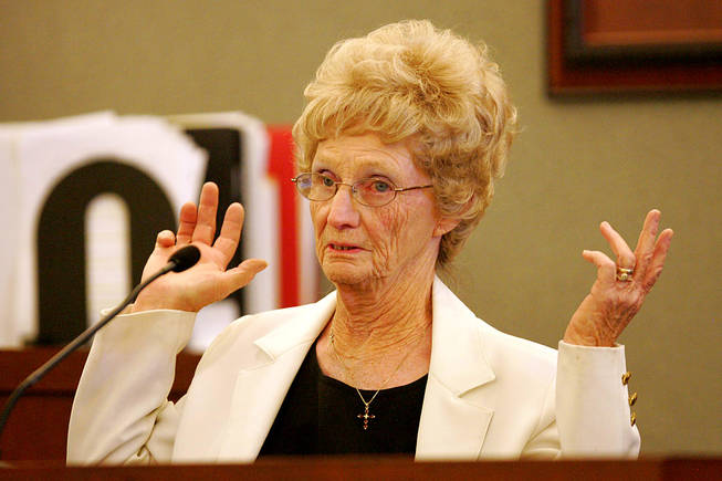 "Eileen Nelson testifies during a coroner's inquest for Erik Scott at the Regional Justice Center Saturday, September 25, 2010. Nelson was describing how after Scott was shot, ""he was stumbling back, with his hands up, empty,"" she said, with her elbows bent and her palms up, demonstrating what she saw."