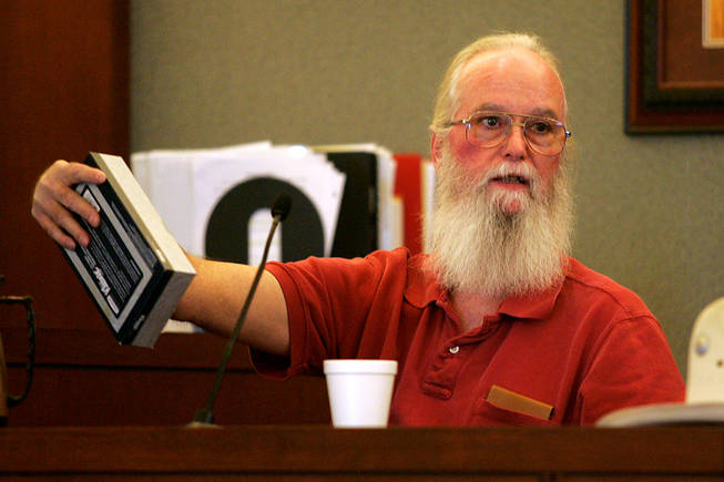 Costco shopper Robert Connolly uses a tissue box to describe the way Erik Scott presented his gun to a Metro officer during a coroner's inquest for Scott at the Regional Justice Center Saturday, September 25, 2010.