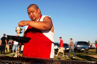 Ronnie Luenza grills Saturday during the tailgating at Star Nursery Fields, north of Sam Boyd Stadium just before the Rebels take on New Mexico.