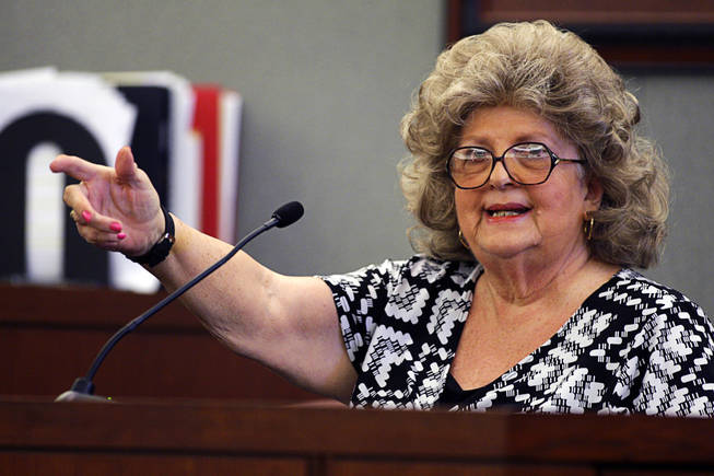 Costco shopper Barbara Fee demonstrates how she saw Erik Scott raise his right arm toward a Metro Police officer as she testifies during a coroner's inquest for Erik Scott at the Regional Justice Center Friday, September 24, 2010.