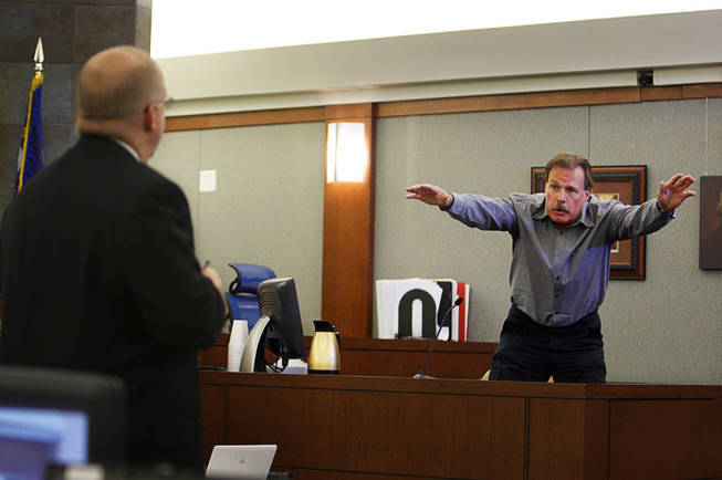 Costco employee Ralph Smithwick demonstrates how Erik Scott reacted after being shot as he testifies during a coroner's inquest for Erik Scott at the Regional Justice Center Monday, September 27, 2010. Chief Deputy District Attorney Christopher Laurent listens at left.