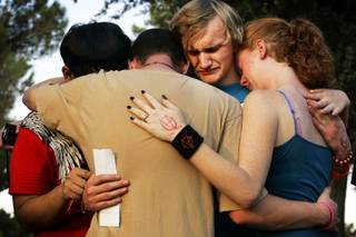 Isaiah Quiambao, 16, from left, Franklin Watkins, 18, Patrick Woodruff, 17, and Crystal Watkins, 16, all students at Chapparal High School and friends of Tanner Chamberlain, embrace during a vigil Wednesday at Sunset Park for Chamberlain on the one-year anniversary of his death. Chamberlain, 15, was shot by a Metro officer as he threatened his mother with a knife, police said.
