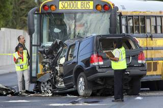 Officials investigate a fatal accident on Decatur Boulevard near Lone Mountain Road Wednesday, October 6, 2010. The driver and a passenger in the sport utility vehicle died, police said. No children were on the bus.