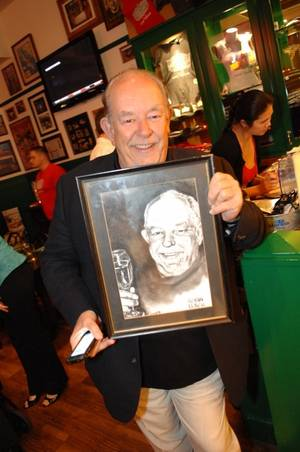 Robin Leach with his charcoal portrait at Hussong's Cantina in Mandalay Place.