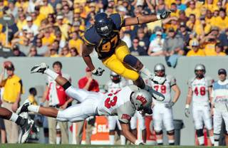 West Virginia's Julian Miller tries to avoid the block by UNLV's Sidney Hodge during an  NCAA college football game Saturday, Oct. 9, 2010 in Morgantown, W.Va.