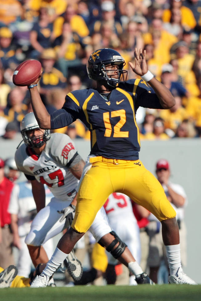West Virginia  quarterback Geno Smith (12) drops back to pass against UNLV  in the second half of an NCAA college football game on Saturday, Oct. 9, 2010 in Morgantown, W.Va.  West Virginia defeated UNLV 49-10.