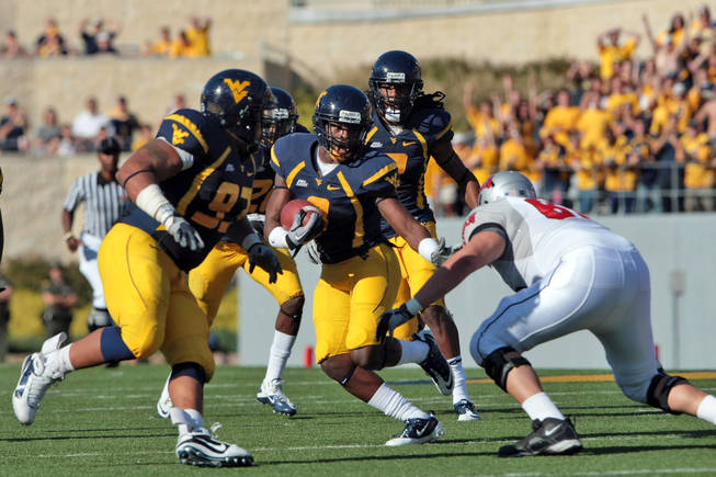 West Virginia's Keith Tandy tries to avoid being tackled by UNLV's John Gianninoto, right,  after an interception during an NCAA college football game in Morgantown, W.Va., Saturday, Oct. 9, 2010. At left is West Virginia's Scooter Berry (93). West Virginia defeated UNLV 49-10.