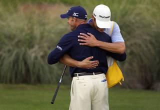 Jonathan Byrd hugs his caddie Adam Hayes after winning the Justin Timberlake Shriners Hospitals for Children Open golf tournament at TPC Summerlin Sunday, October 24, 2010. Byrd made a hole-in-one during a playoff round to beat Cameron Percy and last year's champion Martin Laird.