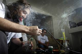 James Parsons, licensed medical marijuana patient and president of Medical Cannabis Consultants of Nevada, smokes marijuana at his home as Licensed medical marijuana patient Justin Martin looks on Tuesday, October 26, 2010.  Parsons was one of several Las Vegans who was targeted by the Drug Enforcement Administration and Metro Police in a crackdown Sept. 8 on individuals who grow marijuana for medicinal purposes. Parsons is legally registered with the state to harvest marijuana for medicinal purposes but his business and Summerlin home were raided. To this day he has still not been charged.