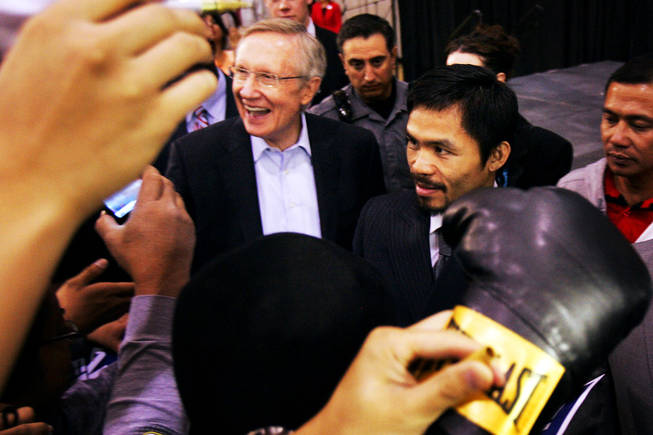 Sen. Harry Reid and boxer Manny Pacquiao sign autographs Friday at Orr Middle School in Las Vegas on Oct. 29, 2010.