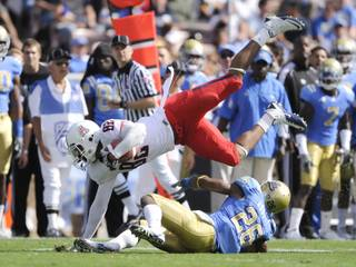 Arizona wide receiver Juron Criner (82) rushes past UCLA cornerback Aaron Hester (21) after the reception during the first half of an NCAA college football game, Saturday, Oct. 30, 2010, in Pasadena, Calif. Arizona won 29-21.