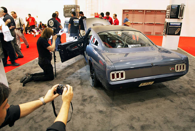 Photographer take photos of a 1965 Ford Mustang customized by the Ring Brothers at the Flowmaster muffler booth during the annual Specialty Equipment Market Association (SEMA) trade show at the Las Vegas Convention Center Wednesday, November 3, 2010.