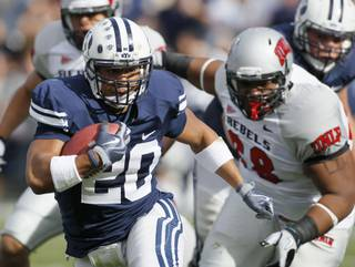 BYU tailback Joshua Quezada (20) rushes for a first down as UNLV defensive lineman Nate Halloway (68) chases during the first half at LaVell Edwards Stadium, Saturday, Nov. 6, 2010, in Provo, Utah. BYU plays in the New Mexico Bowl against UTEP Saturday.