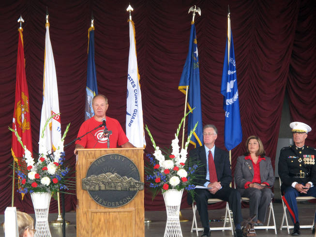 Duane Wagner speaks Saturday at the Henderson Veterans Day Ceremony while, from left, Mayor Andy Hafen, Councilwoman Gerri Schroder and Lt. Col. Michael Viers, from Basic High School's Junior ROTC program, look on. Wagner lost both his legs in Vietnam, but has since ridden a bike across the country.