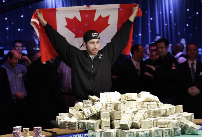 Jonathan Duhamel of Canada holds up a Canadian flag after beating John Racener in the finals of the World Series of Poker Main Event at the Rio on Monday, November 8, 2010. Duhamel won the championship bracelet and $8.9 million in prize money.