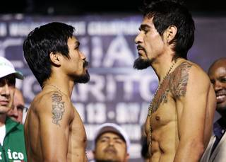 Filipino boxer Manny Pacquiao, left, and Antonio Margarito face off during the official weigh-in in Arlington,Texas Friday, November 12, 2010. Pacquiao weighed in at 144.6 lbs. Margarito weighed the contracted limit of 150 lbs.