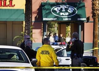Metro Police officers wait outside during an officer-involved shooting investigation at the P.T.'s Pub near Nellis Boulevard and Sahara Avenue on Monday, November 15, 2010. Three Metro Police officers shot and killed a man inside the tavern as the man was holding a bartender at knifepoint during a robbery attempt, police said.