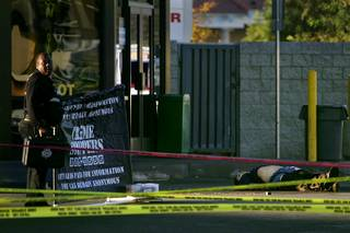 A Metro crime scene investigator moves a barrier into place at the scene of an officer involved shooting outside a Speedee Mart at 3011 East Desert Inn Road Monday, November 15, 2010.