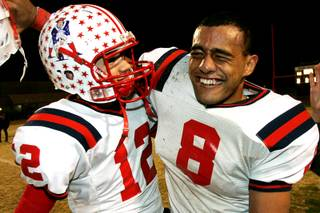 Liberty quarterback Kai Nacua (L) and running back Teu Tai celebrate during the closing minutes of their game against Las Vegas Friday, November 19, 21010. Liberty won 35-14.