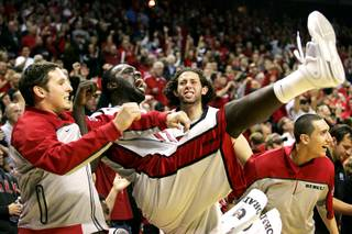 UNLV players, from left, Todd Hanni, Brice Massamba, Carlos Lopez and Karam Mashour celebrate as Justin Hawkins makes a free throw to cement their win over Wisconsin on Saturday. UNLV beat the 25th-ranked Wisconsin 68-65.
