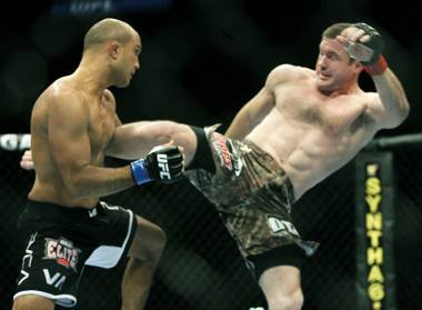 B.J. Penn, left, takes a kick from Matt Hughes during the first round of a welterweight match at UFC 123 in Auburn Hills, Mich. Penn defeated Hughes in 21 seconds of the first round.