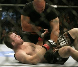 Matt Hughes, bottom, looks up at the referee after his bout was stopped 21 seconds into the first round during a welterweight mixed martial arts match against BJ Penn at UFC 123 on Saturday in Auburn Hills, Mich. Penn was declared the winner.