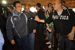 WBA/WBO lightweight champion Juan Manuel Marquez, left, of Mexico greets a fan as he arrives for a pre-fight press conference in the lobby of the MGM Grand Tuesday, November 23, 2010. Marquez will defend his titles against Michael Katsidis of Australia at the MGM Grand Garden Arena on Saturday.