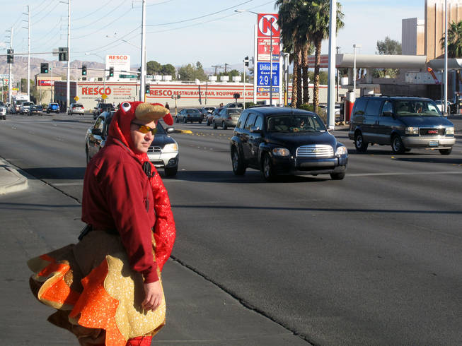 Officer Michael Lemley waits to cross Charleston Boulevard dressed in a turkey costume as part of an enforcement campaign Tuesday.