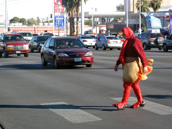 Officer Michael Lemley crosses Charleston Boulevard dressed in a turkey costume as part of an enforcement campaign Tuesday.