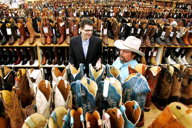 Boot Barn salesman Michael Hull teaches Las Vegas Sun columnist John Katsilometes about cowboy boots as he gets outfitted for the National Finals Rodeo on Wednesday, Nov. 24, 2010.