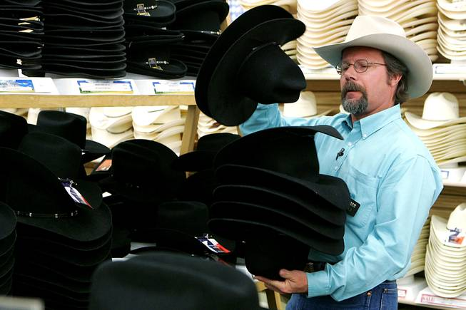Boot Barn salesman Michael Hull looks through cowboy hats for Las Vegas Sun columnist John Katsilometes as he gets outfitted for the National Finals Rodeo on Wednesday, Nov. 24, 2010.