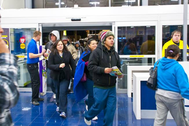 Eager shoppers rush inside Best Buy to grab a deal during a 5 a.m. Black Friday sale, Nov. 26, 2010.