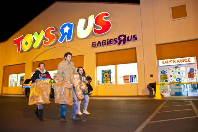 Shoppers leave with bags of toys and games after braving the cold for as long as 3 hours while waiting in line outside Toys R Us on Thursday, Nov. 25, 2010.