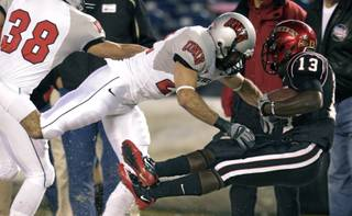 San Diego State running back Ronnie Hillman gets drilled out of bounds by UNLV's Alec DeGiacomo after gaining 15 yards in the first quarter of a NCAA college football game, Saturday, Nov. 27, 2010, in San Diego.