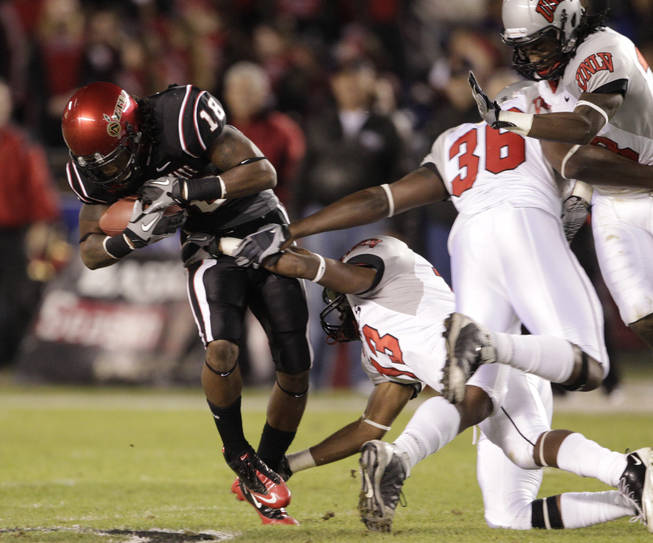 San Diego State's Dominque Sandifer breaks the tackles of UNLV's Eric Tuiloma, left, and Ronnie Paulo while gaining 20 yards on a pass reception during the first quarter of an NCAA college football game, Saturday, Nov. 27, 2010, in San Diego.