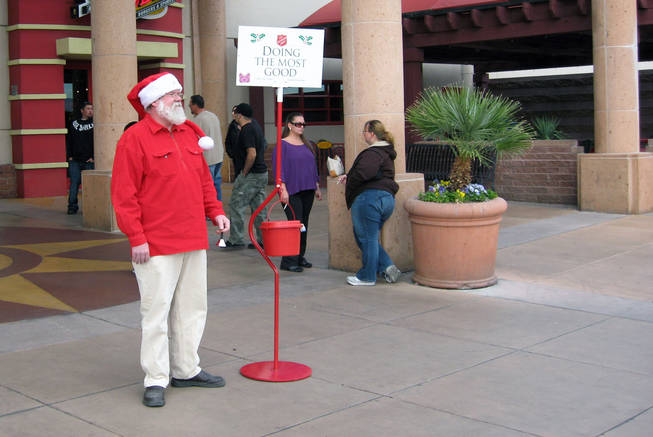 Volunteer Mark Harmon rings a bell to get donations for a Salvation Army red kettle Saturday outside an entrance to the Galleria at Sunset mall in Henderson.