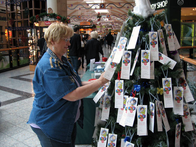 Bonnie Harmon arranges gift tags Saturday on the Angel Tree inside the Galleria at Sunset mall in Henderson. The Salvation Army asks people to pick a gift tag, buy the gift and return it to the organization, which will deliver it to a needy child for Christmas.