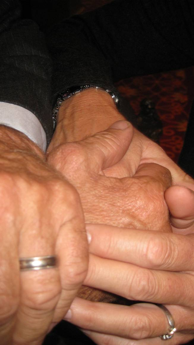 Larry Mahan's hands, showing the thumb that has weathered more than 1,200 rodeos, with those of his wife, Julanne.