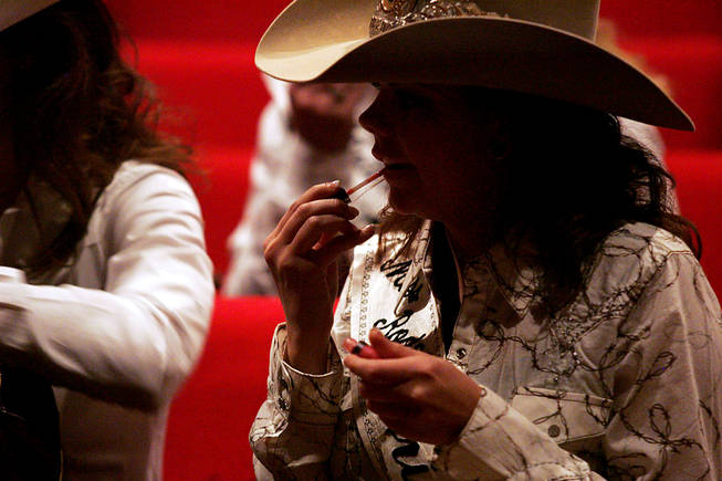 Miss Rodeo Arizona Kasey Jo Painter applies lip gloss while taking a break in rehearsal for the Miss Rodeo America Pageant on Wednesday, Dec. 1, 2010.