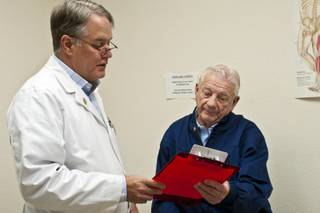 Dr. Frank Redfern explains to his patient, Walter Graham, the importance of a petition asking Congress to reverse planned cuts in Medicare reimbursements, Tuesday, November 30th, 2010.