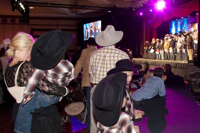 Fans of all ages watch their favorite competitor take the stage during the National Finals Rodeo welcome reception at South Point on Tuesday, Nov. 30, 2010.