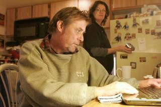 Rodger Jacobs checks his email while Lela Michael works on getting dinner ready in their apartment Thursday, December 2, 2010.
