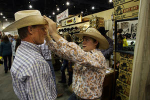 Adam Fitze, right, 18, gives advice to his father Dennis Fitze on how to shape his hat during the Cowboy Christmas Gift Show at the Las Vegas Convention Center on Dec. 3, 2010. The show, affiliated with the Wrangler National Finals Rodeo, runs through Dec. 11.