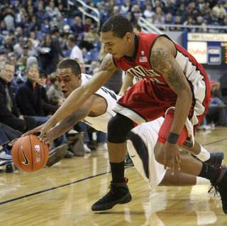 Nevada Wolf Pack guard Jordan Burris battles UNLV Rebels guard Anthony Marshall for the ball in the second half of Saturday night's game in Reno.