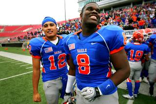 Bishop Gorman quarterback Anu Solomon (L) and defensive end Jalen Grimble smile as they watch the final seconds tick away during their state championship football game against McQueen Saturday, December 4, 2010 at Sam Boyd Stadium. Gorman won 40-0 for back-to-back championships and their third in four years.