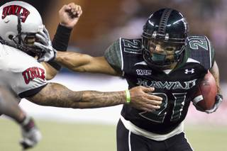 Hawaii slotback Kealoha Pilares stiff arms UNLV defensive back Eric Tuiloma during Saturday's game at Aloha Stadium in Honolulu.