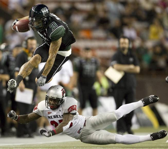 Hawaii slotback Kealoha Pilares leaps over UNLV defensive back Mike Grant during the first quarter of Saturday's game at Aloha Stadium in Honolulu.