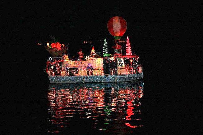 A lighted houseboat sails past Boulder Beach on Saturday, Dec. 4, 2010, at Lake Mead's Christmas Parade of Lights.