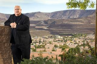 Architect Robert Fielden poses in Henderson December 9, 2010. In the background, the Crystal Ridge development carved terraces into the mountain for custom home sites.