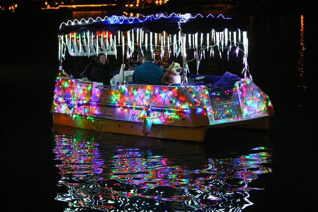 Boats donning sparkling lights participate in the the annual Festival of Lights on Saturday at The Lakes.